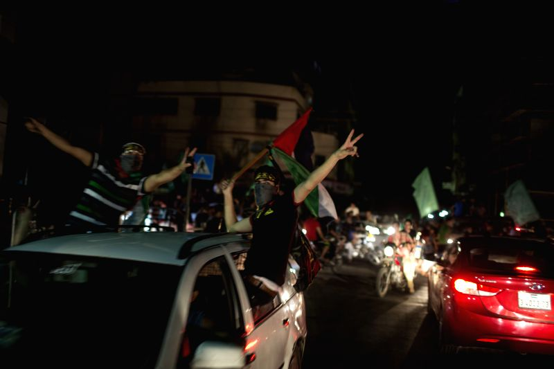 Palestinians celebrate the ceasefire between Palestinians and Israelis in Gaza City, on Aug. 26, 2014. A new Gaza ceasefire came into effect on Tuesday at 7:00 p.m. ...