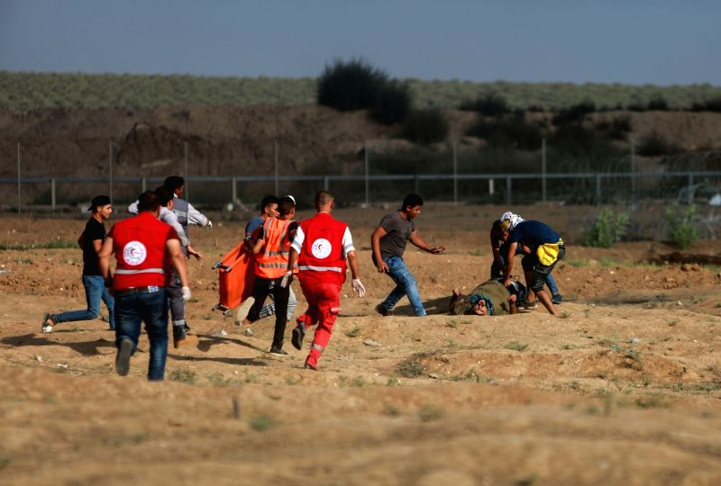 GAZA, Aug. 3, 2018 - Palestinian medics run to help a wounded man during clashes with Israeli troops on the Gaza-Israel border, east of Gaza City, on Aug. 3, 2018. A Palestinian was killed and 220 ...