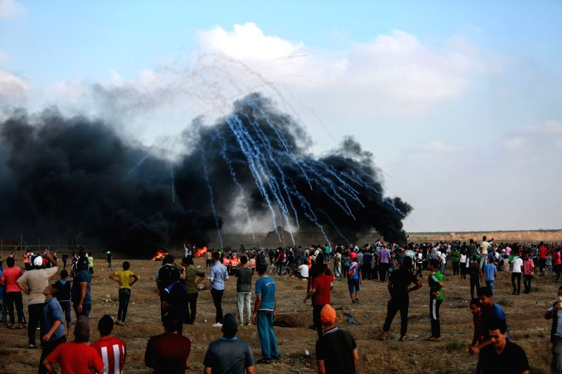 GAZA, Aug. 3, 2018 - Palestinian protesters gather as a shower of tear gas canisters fired by Israeli troops land on the field during clashes on the Gaza-Israel border, east of Gaza City, on Aug. 3, ...