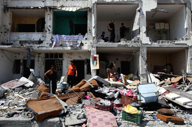 Palestinians collect belongings from their destroyed house after an Israeli strike, in Khuzaa village, east of Khan Younis, in the southern Gaza Strip, on Aug. 5, 2014.
