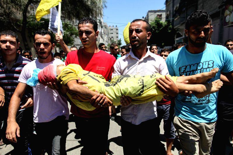 Palestinian mourners carry the body of Palestinian boy Ibrahim al-Dawawsa, 10, who was killed in an Israeli air strike in the northern Gaza City neighborhood of Sheikh .