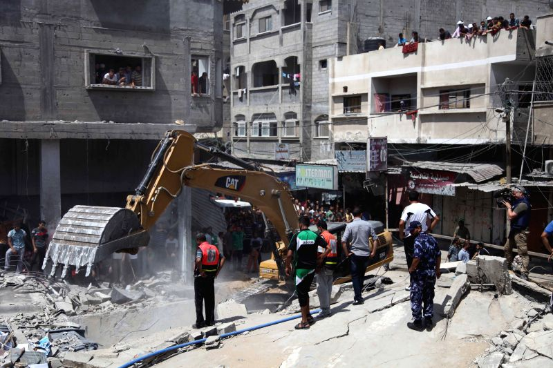 A bulldozer clears away rubble at the al-Qassam Mosque, which was destroyed overnight by an Israeli airstrike that also killed three Palestinians, in the al-Nuseirat ...