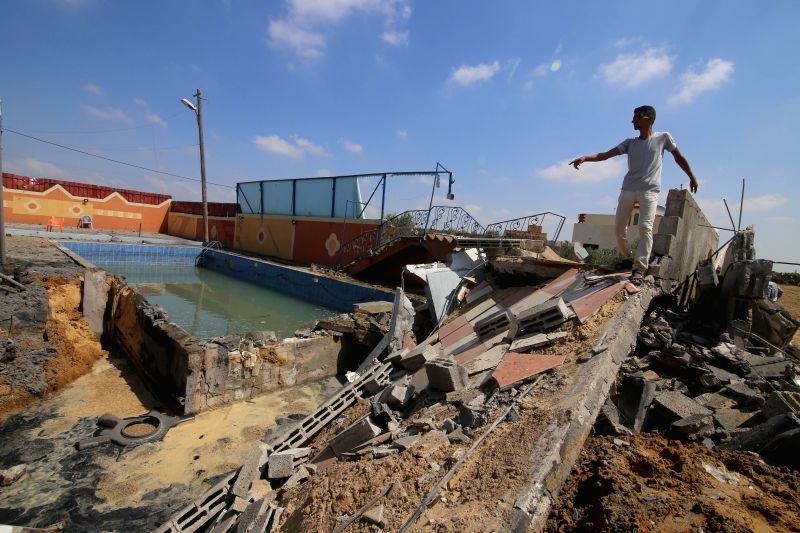 GAZA, Aug. 9, 2018 - A Palestinian man inspects a damaged swimming pool at a tourist resort after it was hit earlier by an Israeli air strike, in the southern Gaza Strip City of Khan Yunis, on Aug. ...