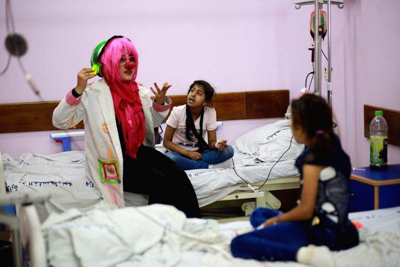GAZA, Aug. 9, 2018 - Dina Nassar (1st L), entertains children, who are cancer patients, in her clown costume inside a hospital in Gaza City, Aug. 8, 2018. Five years ago after Dina's father died of ...