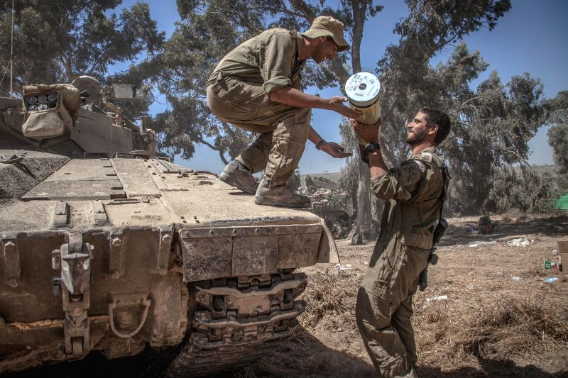 An Israeli soldier hands a shell to another on a Merkava tank at an army deployment area in southern Israel near the border with Gaza, on July 31, 2014. The ...