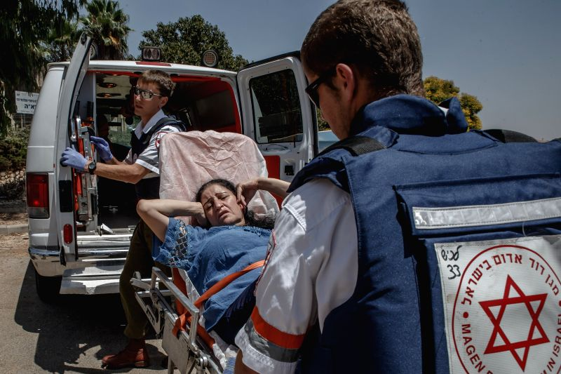 An Israeli woman receives medical assistance after a rocket fired from Gaza Strip fell outside a school in the southern Israeli city of Sderot,  on July 31, ...