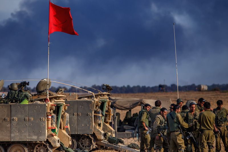 Israeli soldiers are seen at an army deployment area in southern Israel near the border with Gaza, as smoke billows from northern Gaza Strip, on July 31, 2014. ..