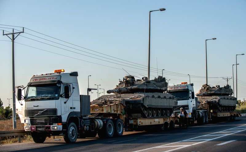 People repair a truck carrying a Merkava tank by the road in southern Israel bordering the Gaza Strip, on Aug. 20, 2014. Israel will step up the offensive in ... - Benjamin Netanyahu