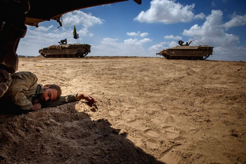 An Israeli soldier sleeps under a military vehicle in south Israel bordering the Gaza Strip after they returned from the Palestinian enclave Aug. 4, 2014. Israel