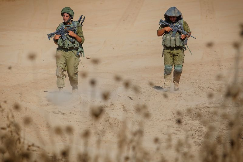 Israeli soldiers walk in south Israel bordering the Gaza Strip after they returned from the Palestinian enclave Aug. 4, 2014. Israel has accepted an Egyptian ...