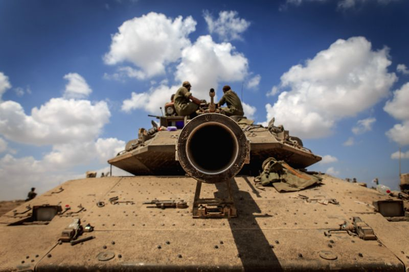 Israeli soldiers sit atop of a Merkava tank in south Israel bordering the Gaza Strip after they returned from the Palestinian enclave Aug. 4, 2014. Israel has ...