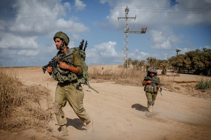 Israeli soldiers walk in southern Israel bordering the Gaza Strip as they return from Gaza, on Aug. 4, 2014. The Israeli military said Tuesday morning it has ...