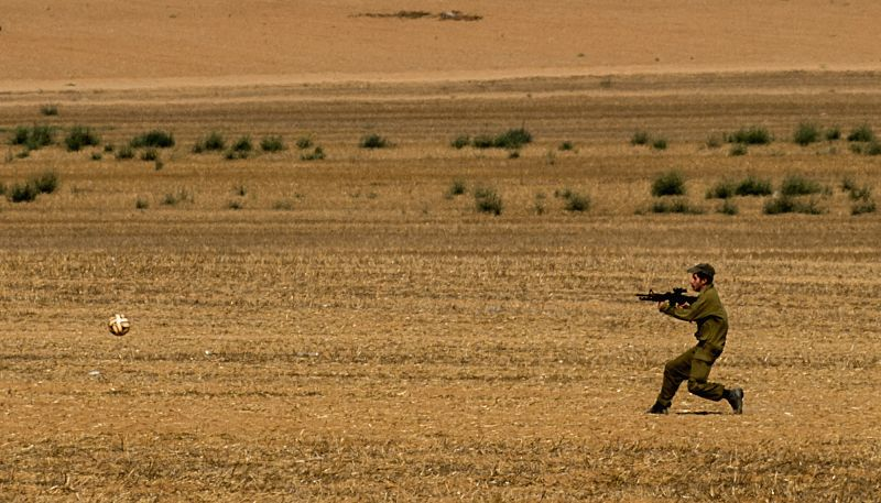 A soldier kicks a ball in south Israel bordering the Gaza Strip, on Aug. 8, 2014. Israel and the Palestinians have failed to extend the 72-hour truce in the Gaza
