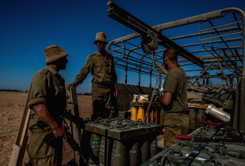 Soldiers unload shells for self-propelled howitzers from a military truck in south Israel bordering the Gaza Strip, on Aug. 8, 2014. Israel and the Palestinians .