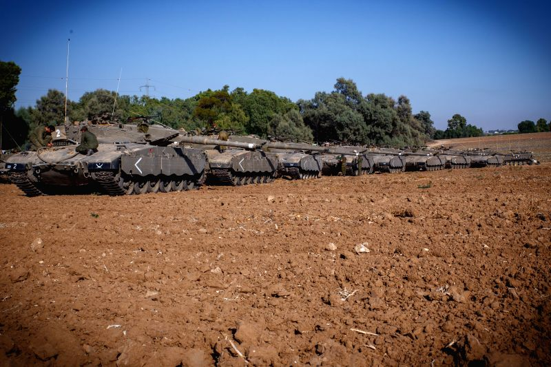 Israeli soldiers work near tanks at a gathering area near the border between Israel and Gaza Strip, on July 10, 2014. Israeli Prime Minister Benjamin Netanyahu . - Benjamin Netanyahu