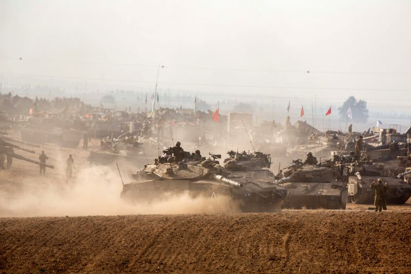 Israeli soldiers work on their Merkava Main Battle Tanks in an army deployment area in Southern Israel near the border with Gaza, on the fifth day of Operation . - Moshe Y
