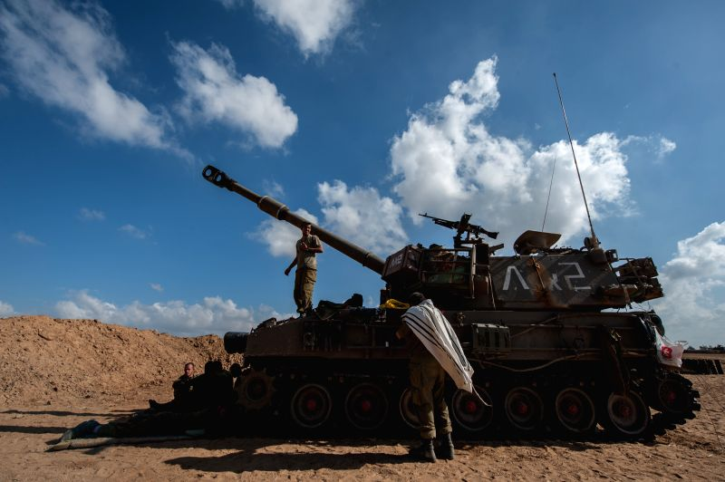 An Israeli Jewish soldier (C, Front) rests in front of a 155mm M109 Dores self-propelled howitzer at a position in Southern Israel near the border with Gaza, on