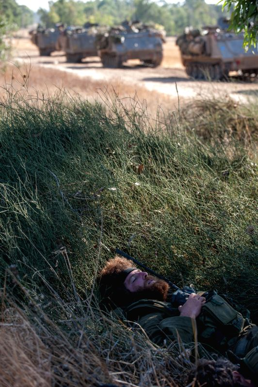 An Israeli soldier takes a nap in the field in southern Israel near the border with Gaza, on the ninth day of Operation Protective Edge, on July 16, 2014. ...