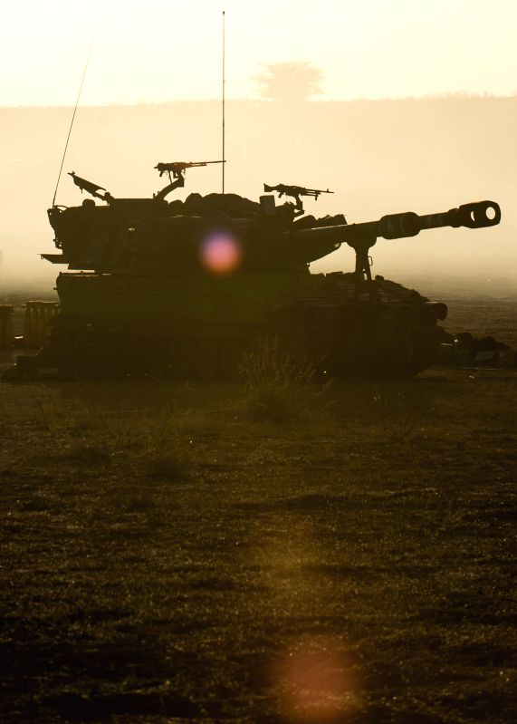 An Israeli self-propelled howitzer is silhouetted against sunrise at a position in southern Israel near the border with Gaza, on the ninth day of Operation ...