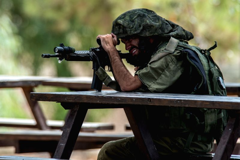 An Israeli soldier aims his weapon to during an operation at an outpost in southern Israel near the border with Gaza, on July 19, 2014, the 12th day of ...