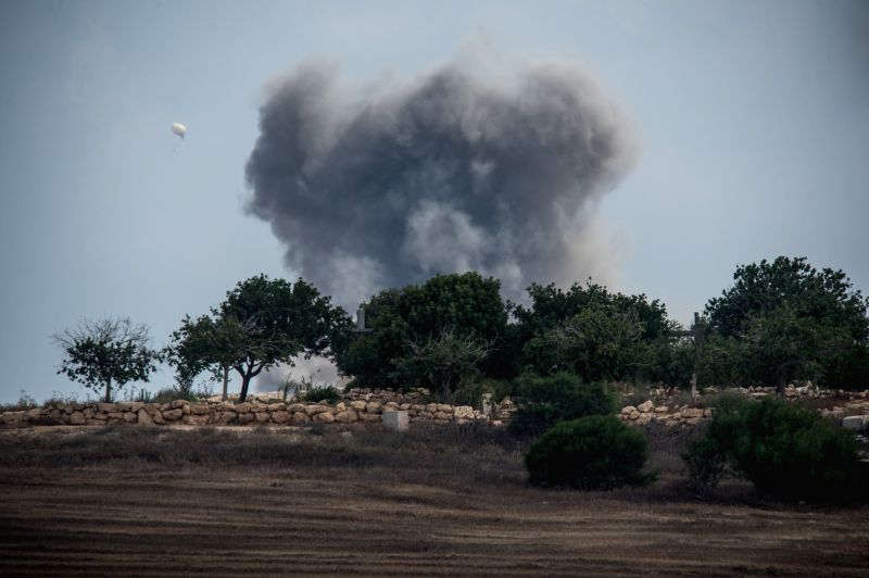 Smoke rises following an Israeli strike in the northern Gaza Strip, seen from an outpost in southern Israel near the border with Gaza, on July 19, 2014, the ...