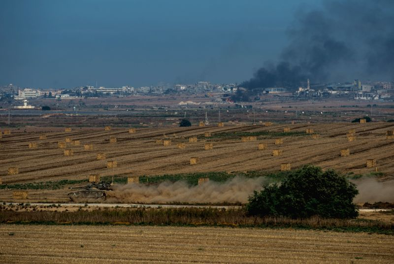 An Israeli Merkava tank runs in the field in southern Israel near the border with Gaza while smoke rises in northern Gaza Strip, on July 30, 2014. Three Israeli