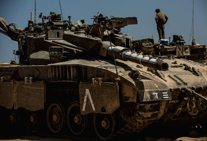 An Israeli soldier stands on a Merkava tank at an army deployment area in southern Israel near the border with Gaza, on July 30, 2014. The Israel Defense Forces