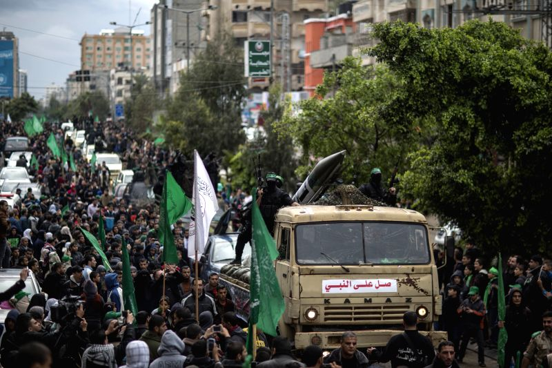 Palestinians and members of al-Qassam Brigades, the armed wing of the Hamas movement, take part in a military parade marking the 27th anniversary of Hamas founding, in