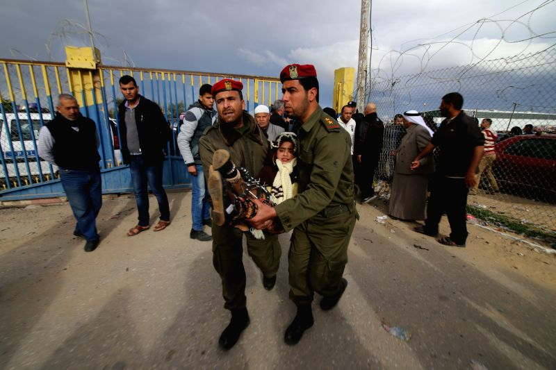 Members of the Palestinian security forces carry a girl, who needs to receive medical treatment outside Gaza, as she waits to cross into Egypt at the Rafah crossing ...