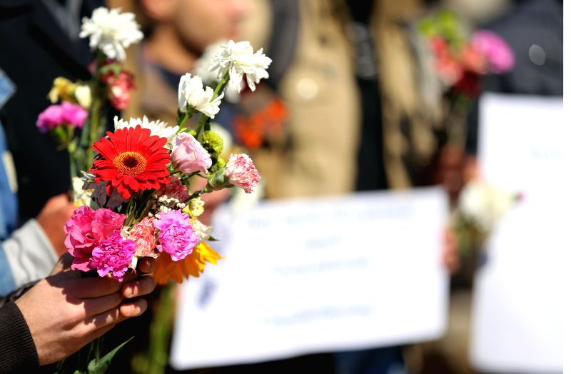 Palestinians carrying flowers gather at the sea of Gaza City, on Feb. 14, 2015, in remembrance of the three Muslim students in North Carolina, the United States. Deah .