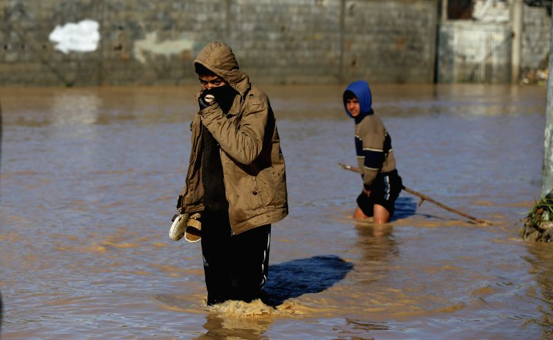 Palestinian Bedouins make their way despite the flood after Israel opened the gates of a dam along its border with the Gaza Strip, in the village of al-Mughraqa, ...