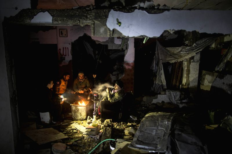 Palestinians warm themselves at their house, which was destroyed during the 50-day conflict between Israel and Hamas, in Gaza City, on Jan. 9, 2015. A powerful storm ..