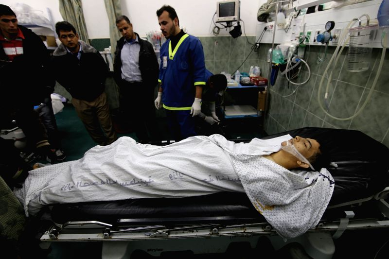 Medic member and relatives gathered around the body of Palestinian Zaki Hobi, 17, at a hospital in the southern Gaza Strip city of Rafah, on Jan 2, 2015. Gaza emergency
