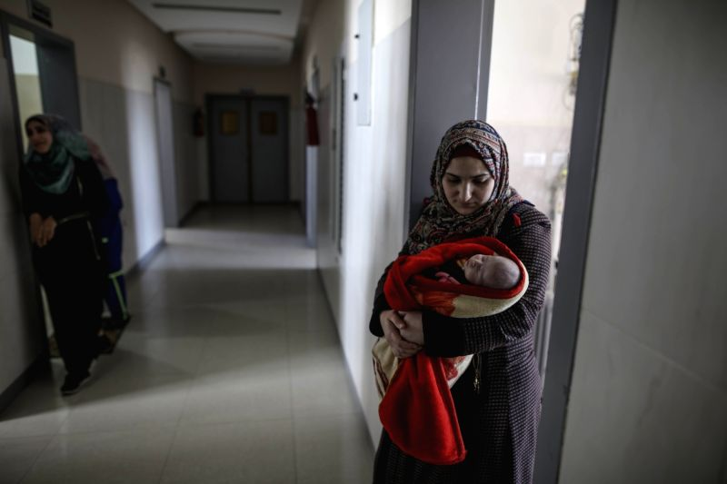 GAZA, Jan. 31, 2018 - A Palestinian woman holds her child at AL Durra Hospital in Gaza Strip, on Jan. 31, 2018. Seven hospitals in the Gaza Strip were forced to suspend services because of the power ...