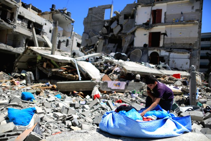A member of the Palestinian Abu Lealla family inspects the remains of their destroyed house following an Israeli airstrike in north of Gaza City on July 11, 2014. ...