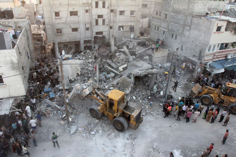 Diggers remove the rubble of a building after it was targeted in an Israeli airstrike early on July 11, 2014, in the southern Gaza strip city of Rafah. At least 88 ...