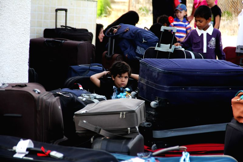 Gaza July 12, 2014  - A Palestinian boy hoping to cross into Egypt sits beside his luggage at the Rafah crossing between Egypt and the southern Gaza Strip on July 12, 2014. Egyptian ...