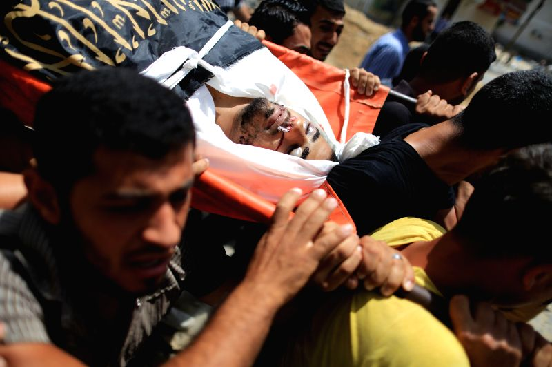 Mourners carry the body of Palestinian Islamic Jihad militant Mohammed Sweilem, who was killed in an Israeli airstrike, at Jabalya refugee camp in the northern Gaza ...