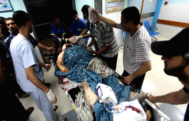Palestinian medics wheel a wounded man on a stretcher into Al-Shifa hospital in Gaza City, July 12, 2014. Gaza Strip police commander and 17 other Palestinians were ...