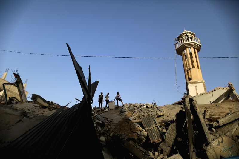 Palestinians inspect the rubbles of a mosque destroyed in an Israeli airstrike at the Nuseirat refugee camp in the central Gaza Strip, July 12, 2014. Gaza Strip police