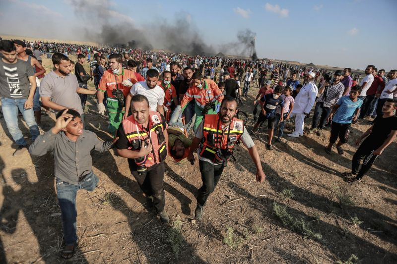 GAZA, July 13, 2018 - Palestinian protesters and medics carry a wounded man during clashes with Israeli troops on the Gaza-Israel border, east of Gaza City, on July 13, 2018. A new round of clashes ...