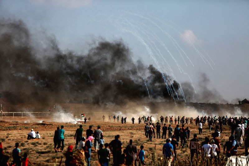 GAZA, July 13, 2018 - Palestinian protesters run to take cover from tear gas canisters fired by Israeli troops during clashes on the Gaza-Israel border, east of Gaza City, on July 13, 2018. A new ...