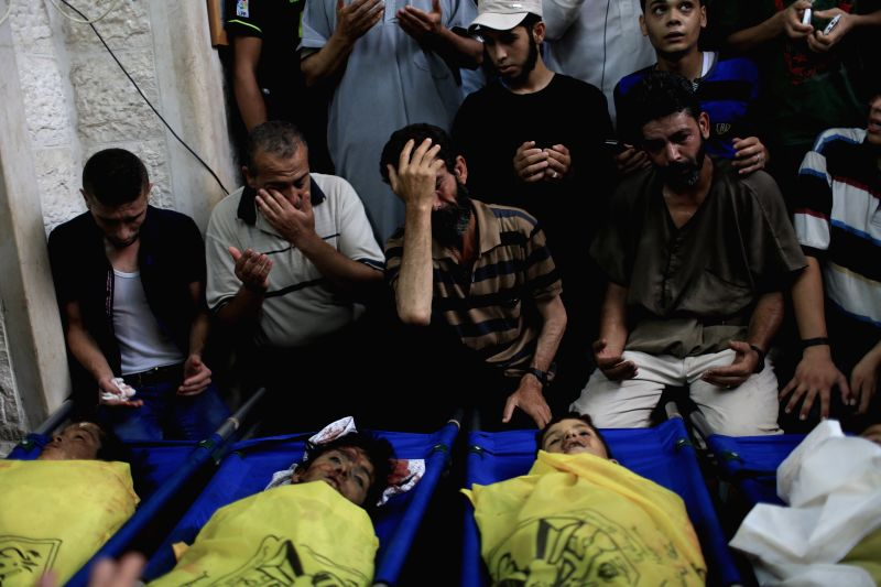 Palestinians gather around the bodies of the boys of Baker family, at a mosque before their funeral in Gaza City, on July 16, 2014. A new Israeli war jets airstrike on