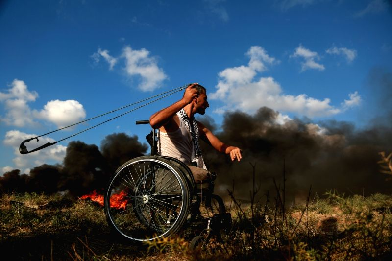GAZA, July 20, 2018 - A Palestinian disabled protester uses a slingshot to hurl stones at Israeli troops during clashes on the Gaza-Israel border, east of Gaza City, on July 20, 2018. Four ...