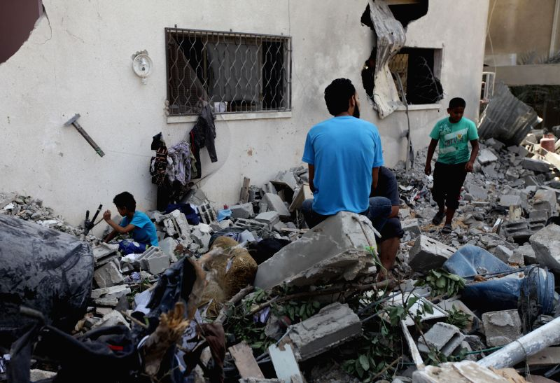Palestinians try to find survivors under the debris of a destroyed house in Al Sheikh Redwan area in the Gaza City, on 21 July 2014. A large-scale Israeli military ...