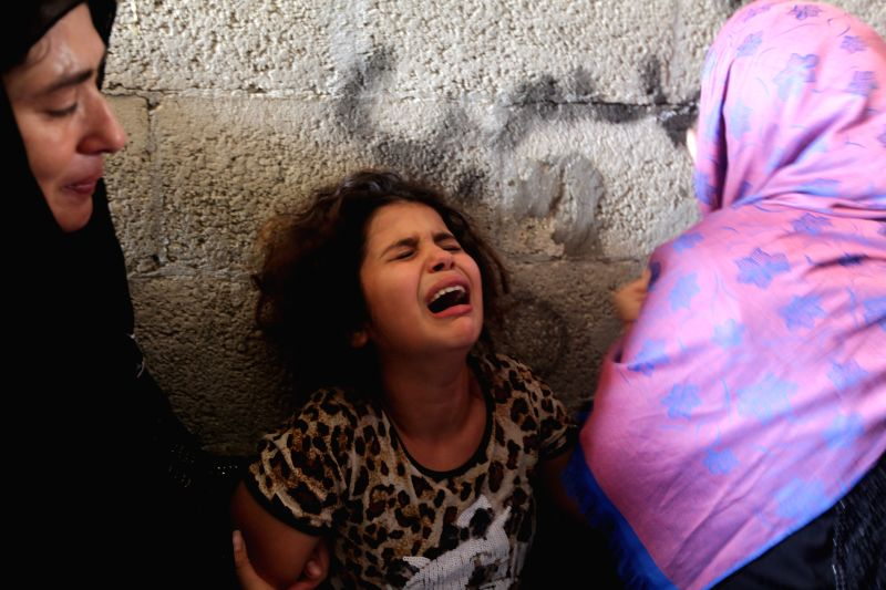 The daughter (C) of Palestinian Hasan Baker, who was killed in an Israeli airstrike, cries during his funeral in Gaza City, on July 22, 2014. So far, more than 600 ...