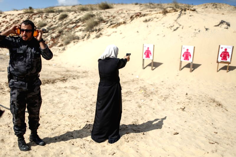 GAZA, July 25, 2016 - A Palestinian girl aims a pistol as she prepares to fire at a target during a training session for the families of Hamas officials, organized by Hamas-run Security and ...