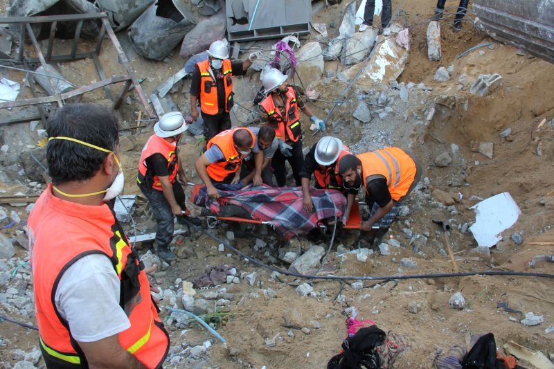 Rescue workers carry the body of a member of al-Najjar family, after removing it from under the rubble of their home following an Israeli air strike on Khan Yunis in ..