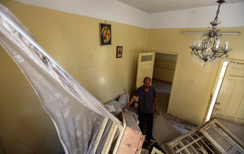 A Relative of Palestinian Jalila Ayad, a Christian woman whose body was found under the rubble of her house, inspects the house after it was damaged by an Israeli ...