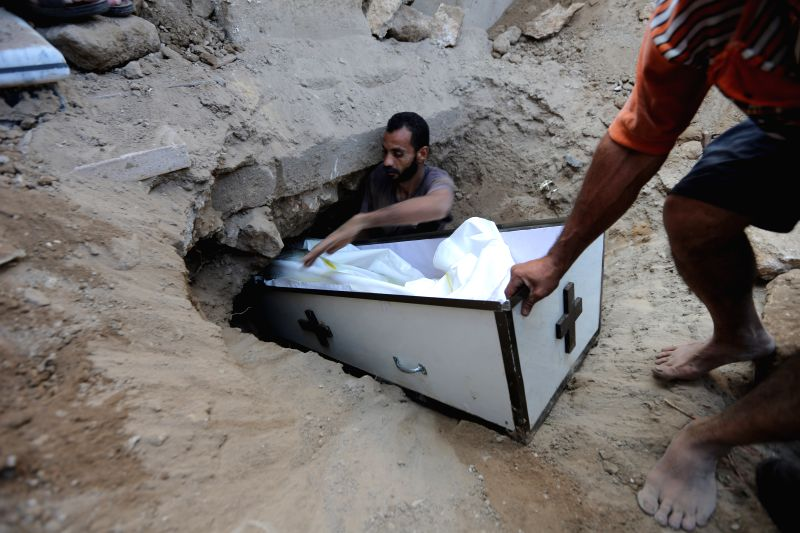 Palestinians bury the coffin of Jalila Ayad, a Christian woman whose body was found under the rubble of her home after an Israeli airstrike, during her funeral in Gaza